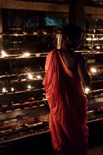 Monje enciende velas