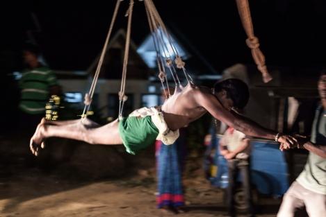 Balanceando a un chico colgado en un Thaipusam